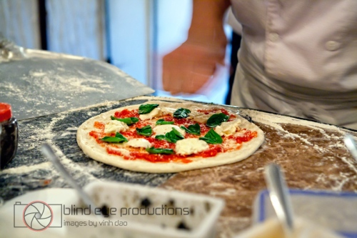 A margherita gets a dash of salt before going in the oven