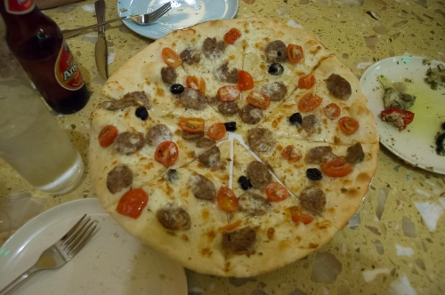 Pizza with sausage, tomatoes, cheese, olives